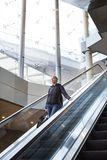 Businesswoman with large black bag and mobile phone descending on escalator. Stock Photo