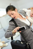 Businesswoman late for work holding her baby Stock Photography