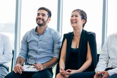 Businesswoman laugh and listen to fun presentation and seminar alongside with male business coworker stock image