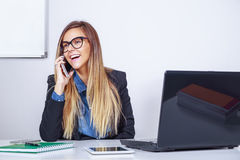 Businesswoman laughing on the mobile phone. Businesswoman in her office laughing on the mobile phone Stock Image