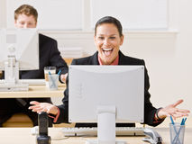 Businesswoman laughing at monitor. Businesswoman laughing her computer monitor Royalty Free Stock Photography