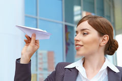 Businesswoman launches paper airplane. Stock Photo