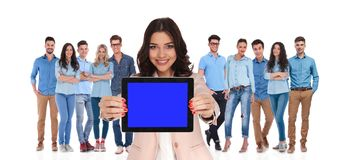 Businesswoman leader of group showing blank screen of tablet. Businesswoman leader of casual group showing blank screen of tablet while standing on white stock photos