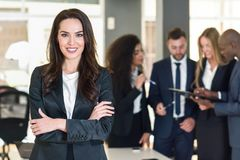 Businesswoman leader in modern office with businesspeople working at background. Businesswoman leader looking at camera in modern office with multi-ethnic stock photo