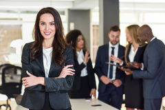 Businesswoman leader in modern office with businesspeople working at background. Businesswoman leader looking at camera in modern office with multi-ethnic stock image