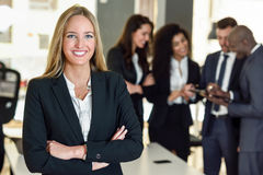Businesswoman leader in modern office with businesspeople working at background. Businesswoman leader looking at camera in modern office with multi-ethnic stock photography