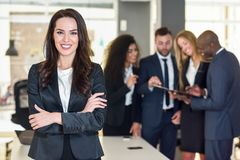 Businesswoman leader in modern office with businesspeople working at background. Businesswoman leader looking at camera in modern office with multi-ethnic royalty free stock image