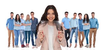Businesswoman leader showing futuristic gadget in front of her g. Businesswoman leader showing futuristic transparent gadget in front of her casual group while stock photography