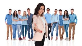 Businesswoman leader welcomes you with a handshake in her group. Businesswoman team leader welcomes you with a warm handshake and a smile in her young casual royalty free stock photography