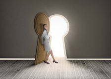Businesswoman leaning against keyhole shaped doorway Stock Photo