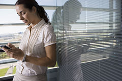 Businesswoman leaning against office window, using personal electronic organiser, side view Stock Photo