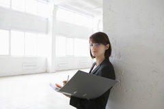 Businesswoman Leaning Against Wall With Paperwork Stock Photo