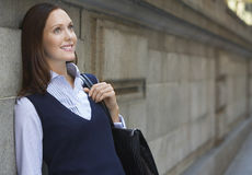 Businesswoman Leaning Against Wall In Street Stock Image
