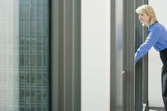 Businesswoman leaning against window sill in office, looking through window, smiling, side view Stock Photo