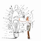 Businesswoman leaning on bulb Stock Photos