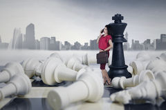 Businesswoman leaning on a chess queen Royalty Free Stock Image