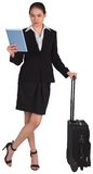 Businesswoman leaning on her suitcase holding tablet pc Royalty Free Stock Image