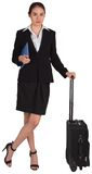 Businesswoman leaning on her suitcase holding tablet pc Stock Photo