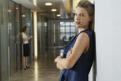 Businesswoman Leaning In Office Corridor Royalty Free Stock Photos