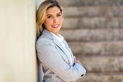 Businesswoman leaning on office wall Royalty Free Stock Image