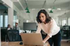 Free Businesswoman Leaning Over Her Office Desk Working On A Laptop Royalty Free Stock Photo - 160060865