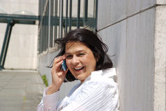 Businesswoman leaning towards wall, on the phone Stock Photo