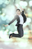 Businesswoman leaps with bokeh background Stock Photography