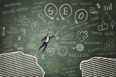 Businesswoman leaps through gap on the blackboard 5 Royalty Free Stock Image
