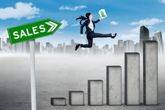 Businesswoman leaps on sales graph Royalty Free Stock Photography