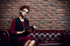 Businesswoman on leather sofa Stock Photography