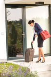 Businesswoman leaving house traveling carrying baggage hurried Stock Photos