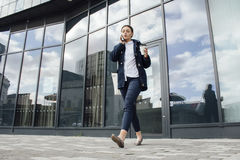 Businesswoman Leaving Work. Young businesswoman is leaving her office building with a cup of tea. She is talking on the phone to someone as she walks royalty free stock photo