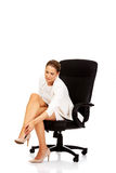Businesswoman with leg pain sitting on the armchair Stock Photo