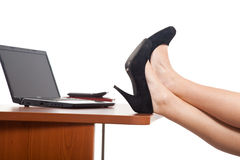 Businesswoman legs on the desk Stock Image