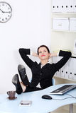 Businesswoman with legs laying on the desk Royalty Free Stock Images