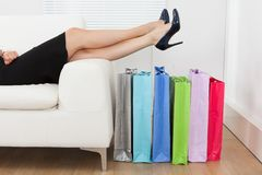 Businesswoman with legs over multi colored shopping bags Royalty Free Stock Images