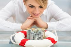 Businesswoman with lifebuoy protecting banknote Stock Photo