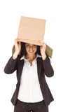 Businesswoman lifting box off head Stock Photo