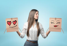 Businesswoman on light blue background holding two carton boxes with drawn lovely faces in her hands. Corporate world. Professional behavior. Business and Royalty Free Stock Photos