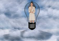 Businesswoman in light bulb surrounded by clouds Stock Photo