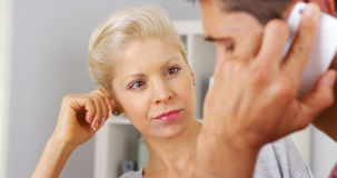 Businesswoman listening in on her colleague's phone conversation Stock Images