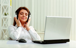Businesswoman listening music in headphones Stock Photos