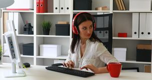 Businesswoman listening music and typing on keyboard. Businesswoman listening music and typing on keyboard stock video