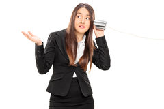 Businesswoman listening through a tin can phone Royalty Free Stock Images