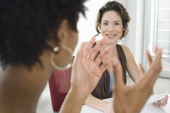 Businesswoman Listening To Female Colleague During Meeting Stock Photography