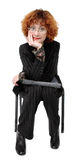 Businesswoman Listens. Redheaded businesswoman in a pinstripe suit, leaning on briefcase in her lap, chin resting in her hand.  Appears to be listening intently Stock Photos