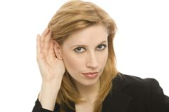 Businesswoman listens. A buinesswoman hold her hand to her ear to hear Stock Photo