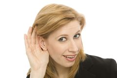 Businesswoman listens. A buinesswoman hold her hand to her ear to hear Stock Photography
