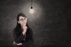 Businesswoman and lit bulb, symbol of idea Stock Photos