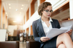 Businesswoman at lobby reading documents Royalty Free Stock Photography